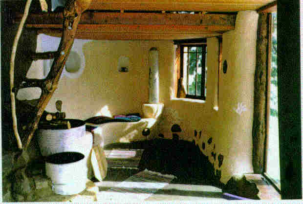 Interior: Barrel stove, heated cob bench, and stabilized earth floor.